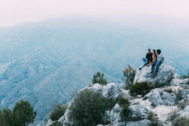 Freunde, die auf felsen in der natur sitzen Kostenlose Fotos