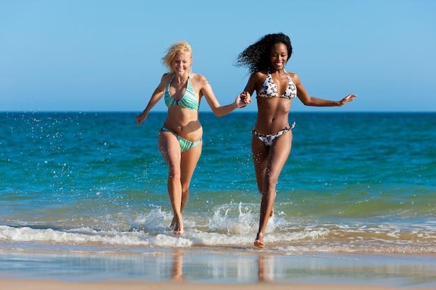 Freunde, die auf strandferien laufen Premium Fotos