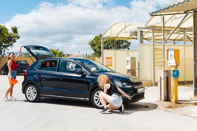 Freunde, die auto beim stoppen an der tankstelle reparieren Kostenlose Fotos