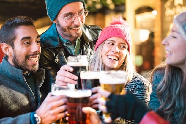 Freunde, die bier trinken und spaß an der brauereibar im freien auf winterzeit haben Premium Fotos
