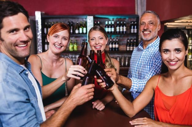 Freunde, die bierflasche im nachtklub rösten Premium Fotos