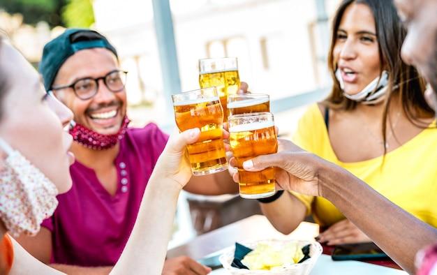 Freunde, die biergläser mit gesichtsmasken rösten - niederländische winkelkomposition mit selektivem fokus auf gläsern Premium Fotos