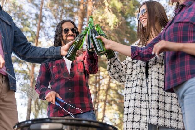 Freunde, die draußen beim grillen mit bier rösten Kostenlose Fotos