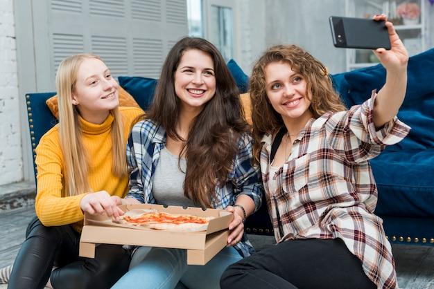 Freunde, die ein selfie essen pizza essen Kostenlose Fotos