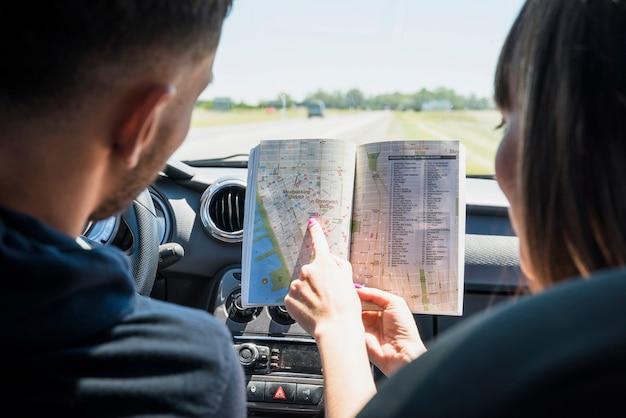 Freunde, die eine bookmap betrachten Kostenlose Fotos