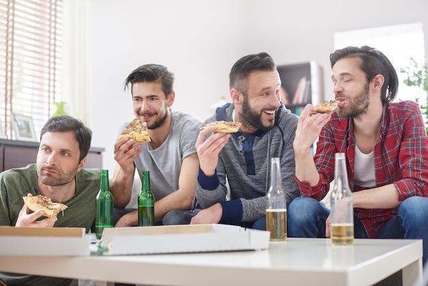 Freunde, die fernsehen und pizza essen Kostenlose Fotos