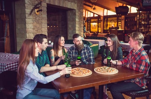 Freunde, die getränke haben und pizza in einer bar essen Premium Fotos