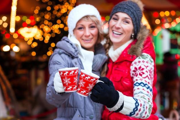 Freunde, die gewürzten wein auf weihnachtsmarkt trinken Premium Fotos
