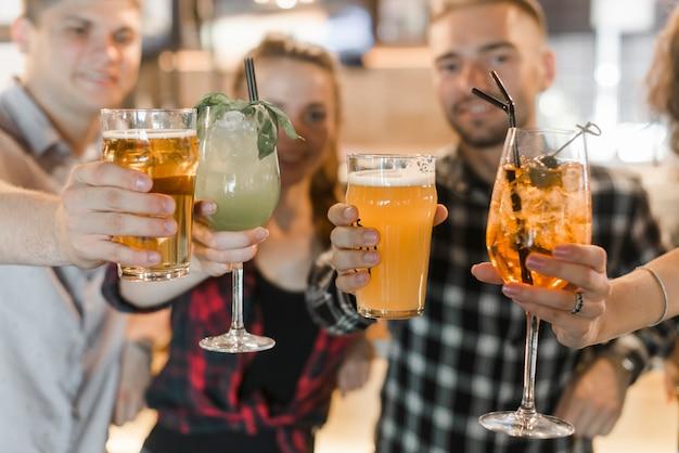 Freunde, die gläser cocktailgetränke zeigen Kostenlose Fotos