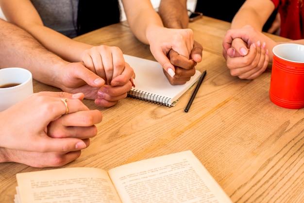 Freunde, die hände nahe briefpapier und kaffeetassen über hölzernem schreibtisch halten Kostenlose Fotos
