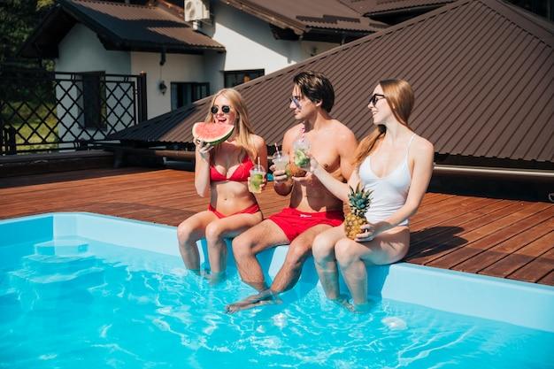 Freunde, die ihren urlaub am pool genießen Kostenlose Fotos