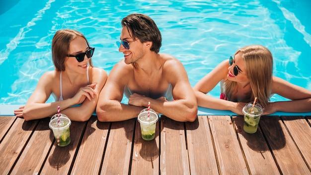 Freunde, die im swimmingpool sprechen Kostenlose Fotos