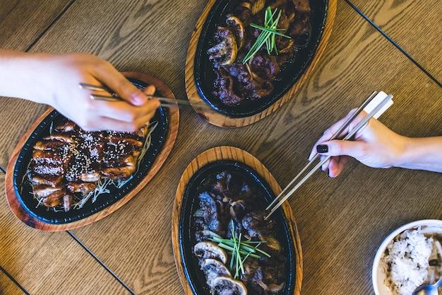 Freunde, die koreanische knusprige ente und bulgogi mit essstäbchen essen Kostenlose Fotos