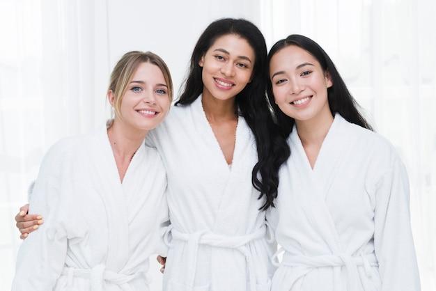 Freunde, die mit bademantel in einem badekurort aufwerfen Kostenlose Fotos