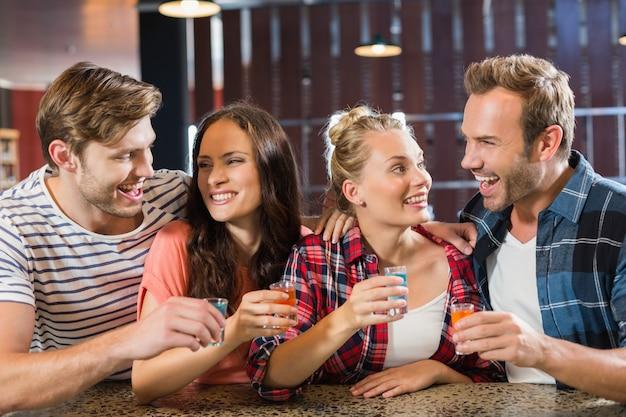 Freunde, die mit schüssen in der hand lachen Premium Fotos