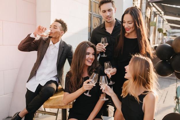 Freunde, die spaß haben und draußen champagner trinken Kostenlose Fotos