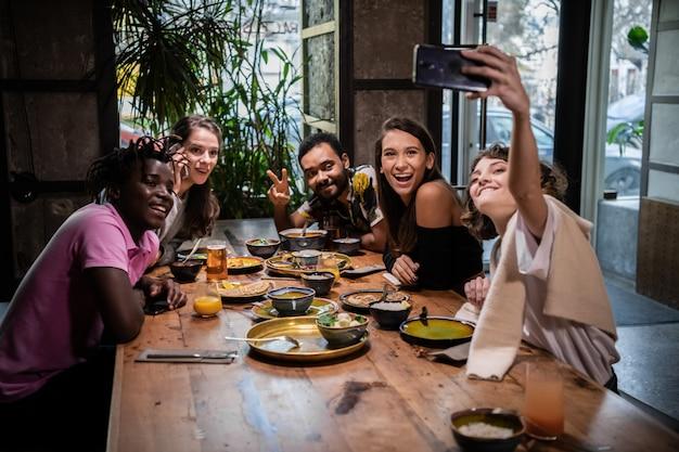 Freunde, die während einer dinnerparty selfies in einem café machen Premium Fotos