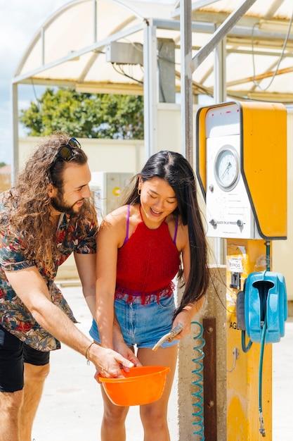 Freunde, die wasser an der tankstelle während des zwischenstopps erhalten Kostenlose Fotos