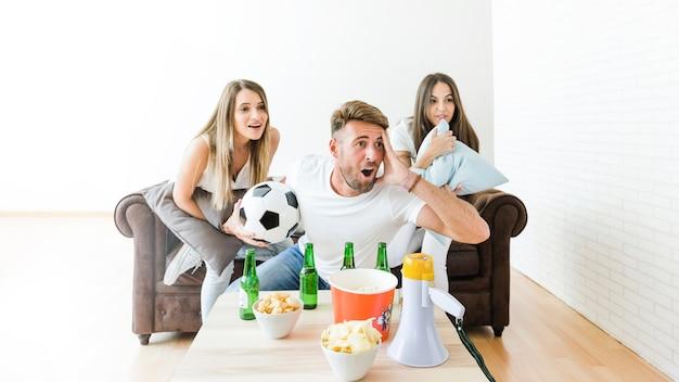 Freunde, die zu hause fußball aufpassen Kostenlose Fotos