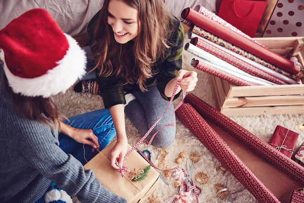 Freunde, die zusammen ein weihnachtsgeschenk machen Kostenlose Fotos