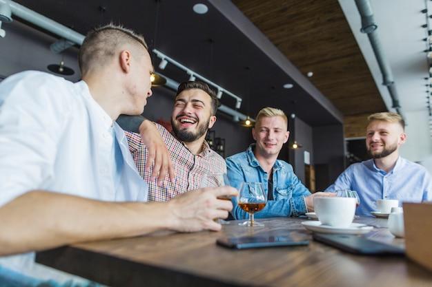 Freunde, die zusammen im restaurant das getränk genießend sitzen Kostenlose Fotos