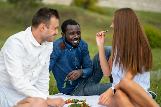 Freunde draußen auf einer decke Kostenlose Fotos