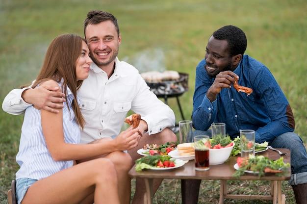 Freunde essen neben dem grillen im freien Kostenlose Fotos