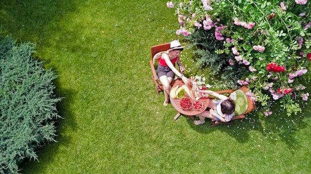 Freunde essen zusammen im freien im sommergarten, mädchen haben picknick im park, luftaufnahme des tisches mit essen und getränken von oben Premium Fotos