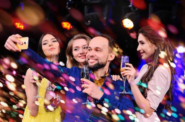 Freunde feiern die veranstaltung, lachen, tanzen und trinken champagner Premium Fotos