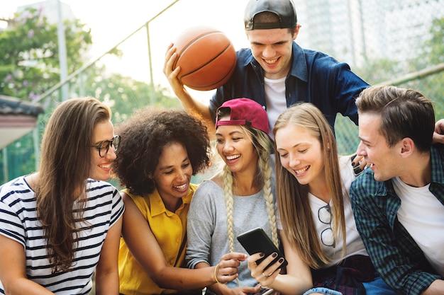 Freunde im park, der unter verwendung der smartphones tausendjähriges und jugendkulturkonzept schaut Premium Fotos