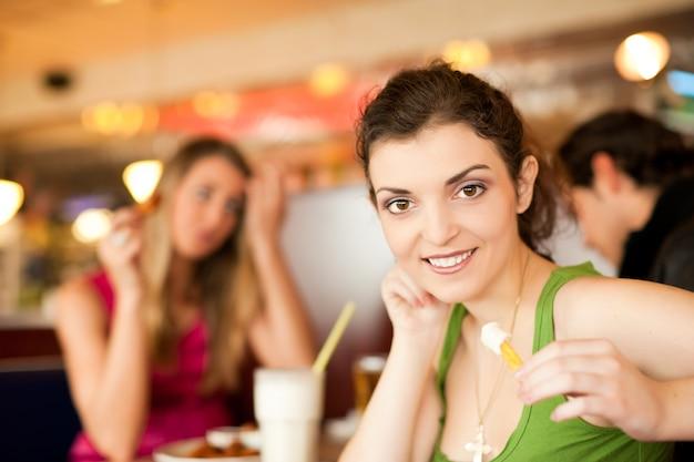 Freunde im restaurant, das schnellimbiß isst Premium Fotos