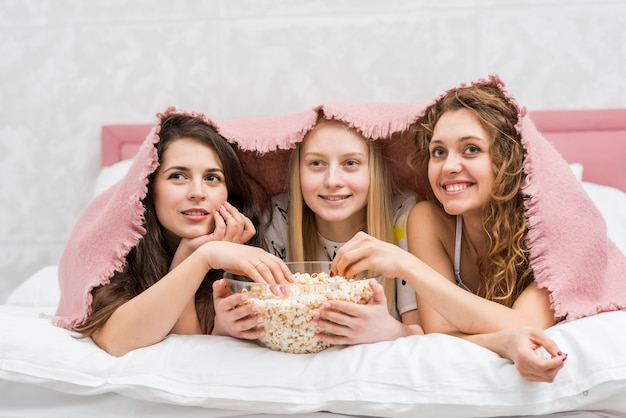 Freunde in der pijama-party popcorn essend Kostenlose Fotos