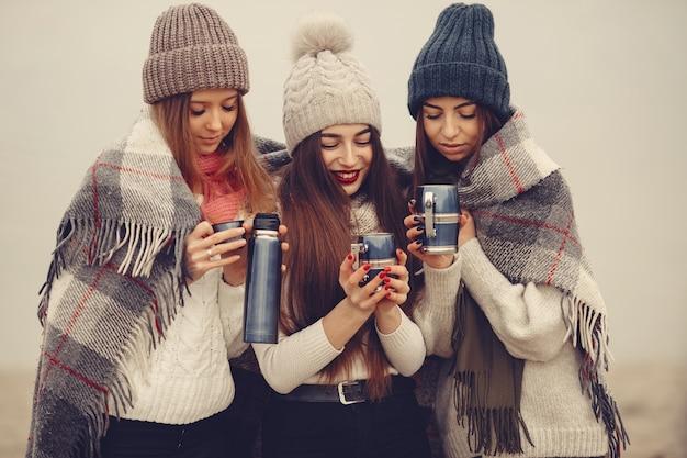 Freunde in einem winterpark. mädchen in strickmützen. frauen mit thermoskanne und tee. Kostenlose Fotos