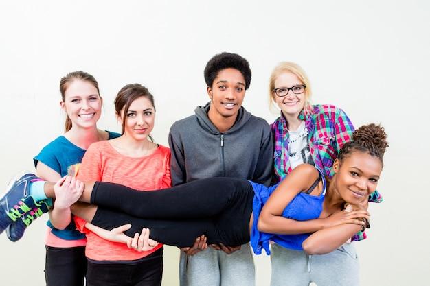 Freunde in tragender frau der tanzklasse auf händen Premium Fotos