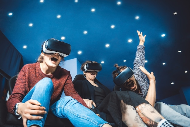 Freunde in virtuellen gläsern schauen sich filme im kino mit spezialeffekten in 5d an Premium Fotos