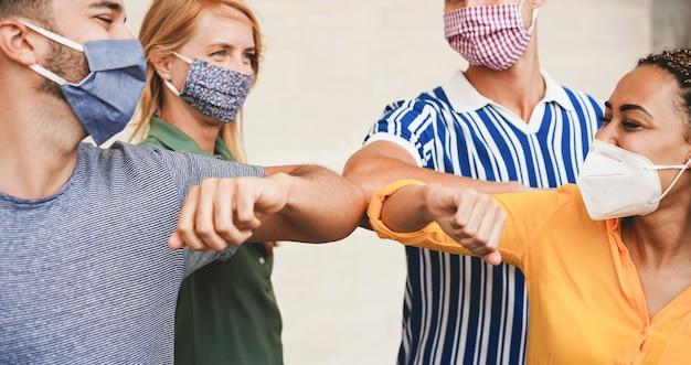 Freunde junger leute stoßen mit den armen, anstatt sie mit einer umarmung zu begrüßen. - vermeiden sie die verbreitung von coronavirus, sozialer distanz und freundschaftskonzept. - konzentrieren sie sich auf nahaufnahmen Premium Fotos