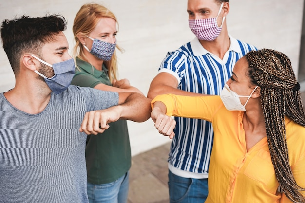 Freunde junger leute stoßen mit den ellbogen, anstatt sie zu umarmen Premium Fotos