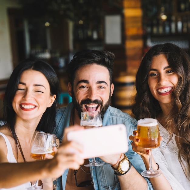 Freunde mit bier posieren für selfie Kostenlose Fotos