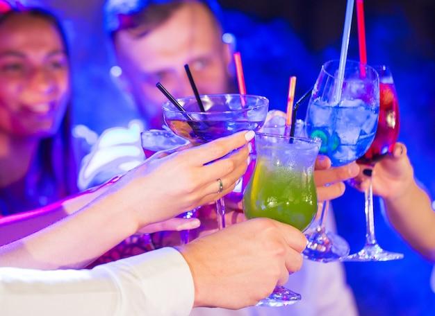 Freunde mit cocktails trinken auf einer party. Premium Fotos