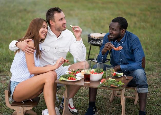 Freunde neben dem grillen essen Kostenlose Fotos