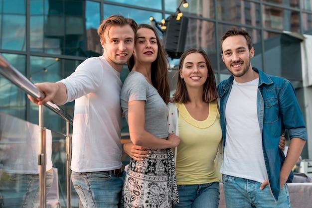 Freunde posieren auf einer terrassenparty Kostenlose Fotos
