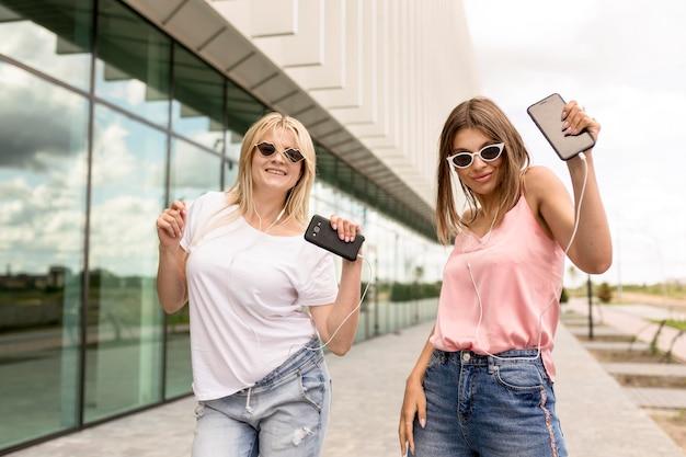 Freunde posieren auf modische weise draußen Kostenlose Fotos