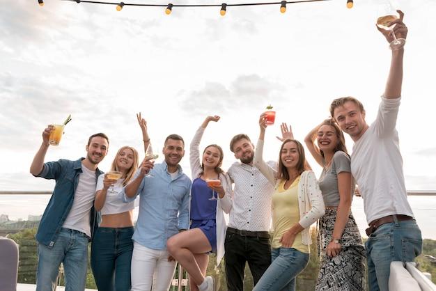 Freunde posieren mit getränken auf einer party Kostenlose Fotos