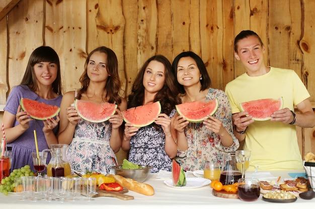Freunde posieren mit wassermelonenscheiben Kostenlose Fotos