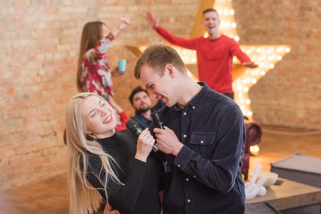 Freunde singen karaoke auf einer party Kostenlose Fotos