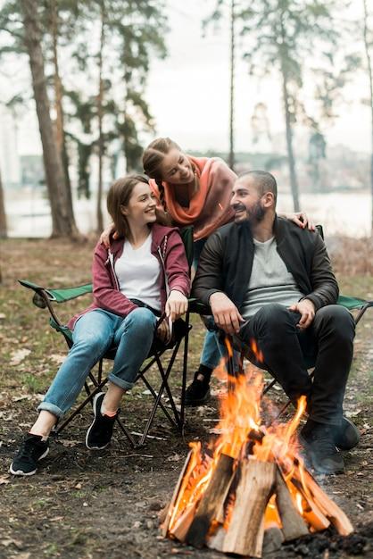 Freunde sitzen am lagerfeuer Kostenlose Fotos