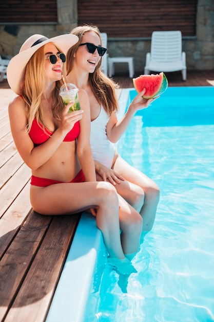Freunde sitzen am rande des pools Kostenlose Fotos