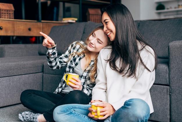 Freunde sitzen auf dem boden mit tee Kostenlose Fotos