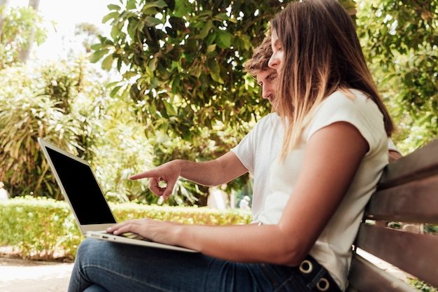Freunde sitzen auf der bank mit einem notebook Kostenlose Fotos
