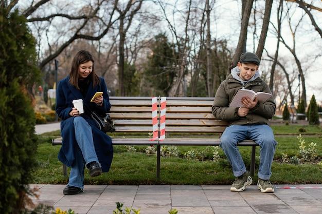 Freunde sitzen in der ferne und tragen maske Kostenlose Fotos